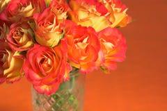 Oranje Rozen in glasvaas Stock Foto's