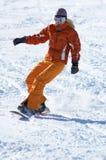 Oranje snowboardmeisje bergaf Stock Foto's