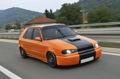 Oranje sportwagenaandrijving snel royalty-vrije stock afbeelding