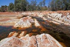 Oranje stenen in Rio Tinto stock afbeeldingen