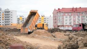 Oranje stortplaatsvrachtwagens die aan een bouwwerf werken stock footage