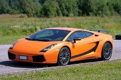 Oranje supercar op een renbaan Stock Fotografie