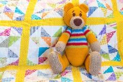 Oranje teddybeerzitting op kleurrijk gewatteerd dekbedovertrek stock foto's