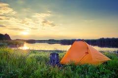 Oranje tent en rugzak op het meer bij zonsondergang Royalty-vrije Stock Afbeelding