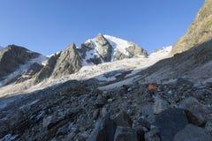 Oranje tent onder stenen in hooglandkamp tegen bergen en Stock Foto's