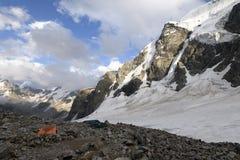 Oranje tent onder stenen in hooglandkamp tegen bergen en Stock Afbeelding