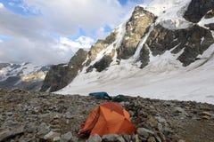 Oranje tent onder stenen in hooglandkamp tegen bergen en Stock Foto