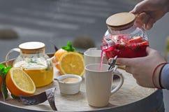 Oranje thee met gember en frambozen op een houten achtergrond Stock Afbeelding
