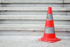 Oranje veiligheidspyloon op treden Stock Fotografie