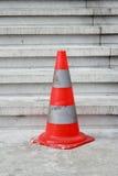 Oranje veiligheidspyloon op treden Stock Afbeelding