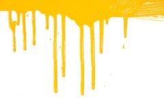 Oranje verf die/druipt die op wit wordt geïsoleerdo Royalty-vrije Stock Afbeeldingen