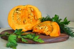 Oranje verse pompoen, met greens besnoeiingsplakken van pompoen op de lijst royalty-vrije stock afbeelding