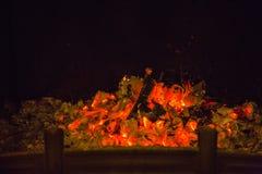 Oranje vlammen in as in open haard Stock Foto's
