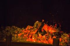 Oranje vlammen in as in open haard Stock Afbeelding
