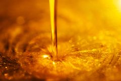 Oranje vloeibare en kleverige stroom van de olie van de motorfietsmotor zoals een stroom van honingsclose-up royalty-vrije stock afbeeldingen