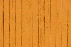 Oranje vlokkige verf op een houten omheining Stock Foto