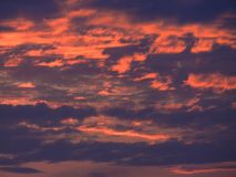 Oranje wolken in purpere zonsondergang royalty-vrije stock foto