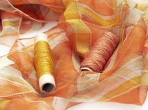 Oranje zijde en aanpassingsdraden stock afbeelding