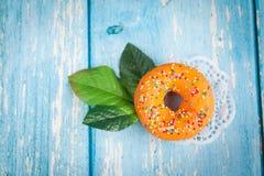 Oranje zoete doughnut met groene bloembladeren Stock Afbeeldingen