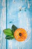 Oranje zoete doughnut met groene bloembladeren Royalty-vrije Stock Foto