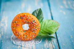 Oranje zoete doughnut met groene bloembladeren Royalty-vrije Stock Afbeelding