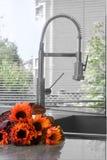 Oranje zonnebloemen door de keukengootsteen Royalty-vrije Stock Foto's