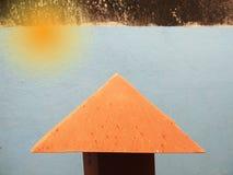 Oranje zonnestraal en dak op blauwe muur stock afbeeldingen