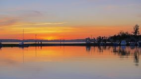Oranje zonsondergang in de jachtclub De boten worden geparkeerd op het water stock footage
