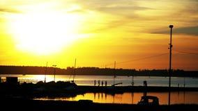 Oranje zonsondergang in de jachtclub De boten worden geparkeerd op het water stock videobeelden