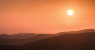 Oranje zonsondergang met heuvels Stock Foto