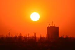 Oranje zonsondergang op de achtergrond van gebouwen Stock Foto's