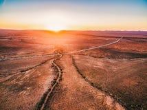 Oranje zonsondergang over droog land en landelijke weg stock foto's