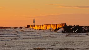 Oranje zonsonderganggloed en golven die tegen golfbreker in de Oostzee bespatten stock afbeelding