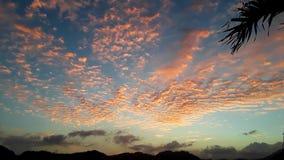 Oranje zonsonderganghemel over de bergen stock foto's