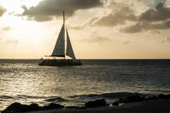 Oranjestad, Aruba - 10. April 2018: Segeln in ein Segelboot nahe Eagle Beach bei Sonnenuntergang Stockbild