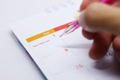 Orario di lavoro di scrittura della penna sul calendario da tavolino Fotografie Stock Libere da Diritti