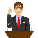 Orator standing behind a podium with microphones Stock Photos