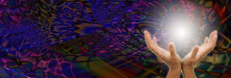 Orb Energy. Female healer with cupped hands sensing a ball of white light on a multi colored wide dark psychedelic energy formation background with copy space on Royalty Free Stock Photo