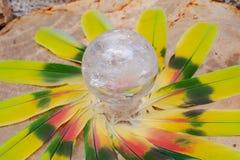 Orb för kristall för sfär för Lemurian frikändkvarts magisk i mitt av en cirkel som göras av färgrika fjädrar arkivbilder