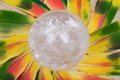 Orb för kristall för sfär för Lemurian frikändkvarts magisk i mitt av en cirkel som göras av färgrika fjädrar arkivfoton