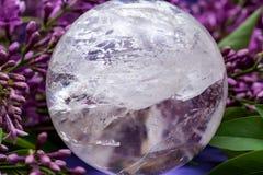 Orb f?r kristall f?r sf?r f?r Lemurian frik?ndkvarts som magisk omges av den purpurf?rgade lila blomman royaltyfria bilder