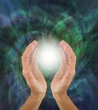 Orb Light Paranormal Phenomenon between hands. Hands cupped around a bright white orb light against a green rotating energy field background with copy space royalty free stock photography