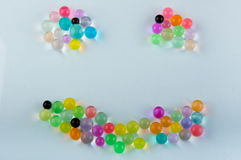 Orbeez hydrogel balls laying in smile shape on white background Stock Images