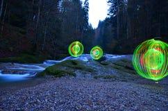 Orbes que brillan intensamente al lado de la cascada Fotografía de archivo libre de regalías