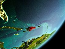 Orbit view of Dominican Republic. Dominican Republic in early morning light highlighted in red on planet Earth with visible border lines and city lights. 3D Royalty Free Stock Photo