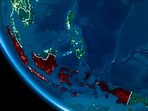 Orbit view of Indonesia at night. Map of Indonesia in red as seen from space on planet Earth at night with white borderlines and city lights. 3D illustration stock photo