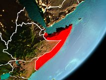 Orbit view of Somalia. Somalia in early morning light highlighted in red on planet Earth with visible border lines and city lights. 3D illustration. Elements of stock photos