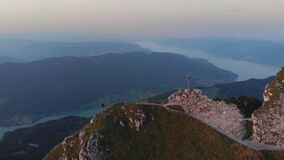 Aerial 4k orbital drone sunset at mountain peak with cross. Hiker girl climbing and taking pictures