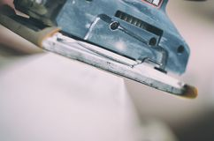 Orbital sander in use, sanding old door for a new lick of paint royalty free stock photo