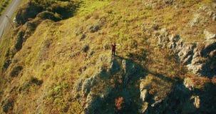 Orbitale radiale vlucht rond de jonge wandelende mens die zich bovenop de klip bevinden Handen omhoog, winnaar stock video